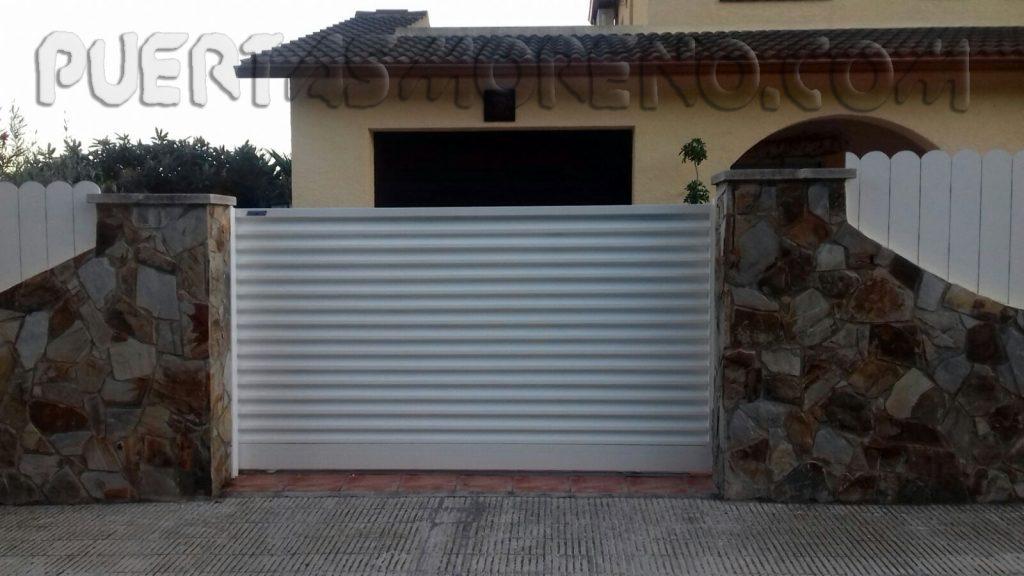Puerta corredera y peatonal veneciana en casa residencial for Puertas venecianas